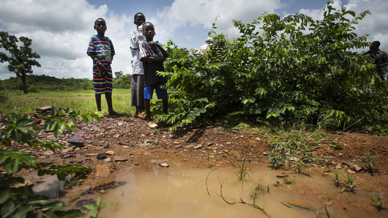 Children look at a contaminated pond in Mali.