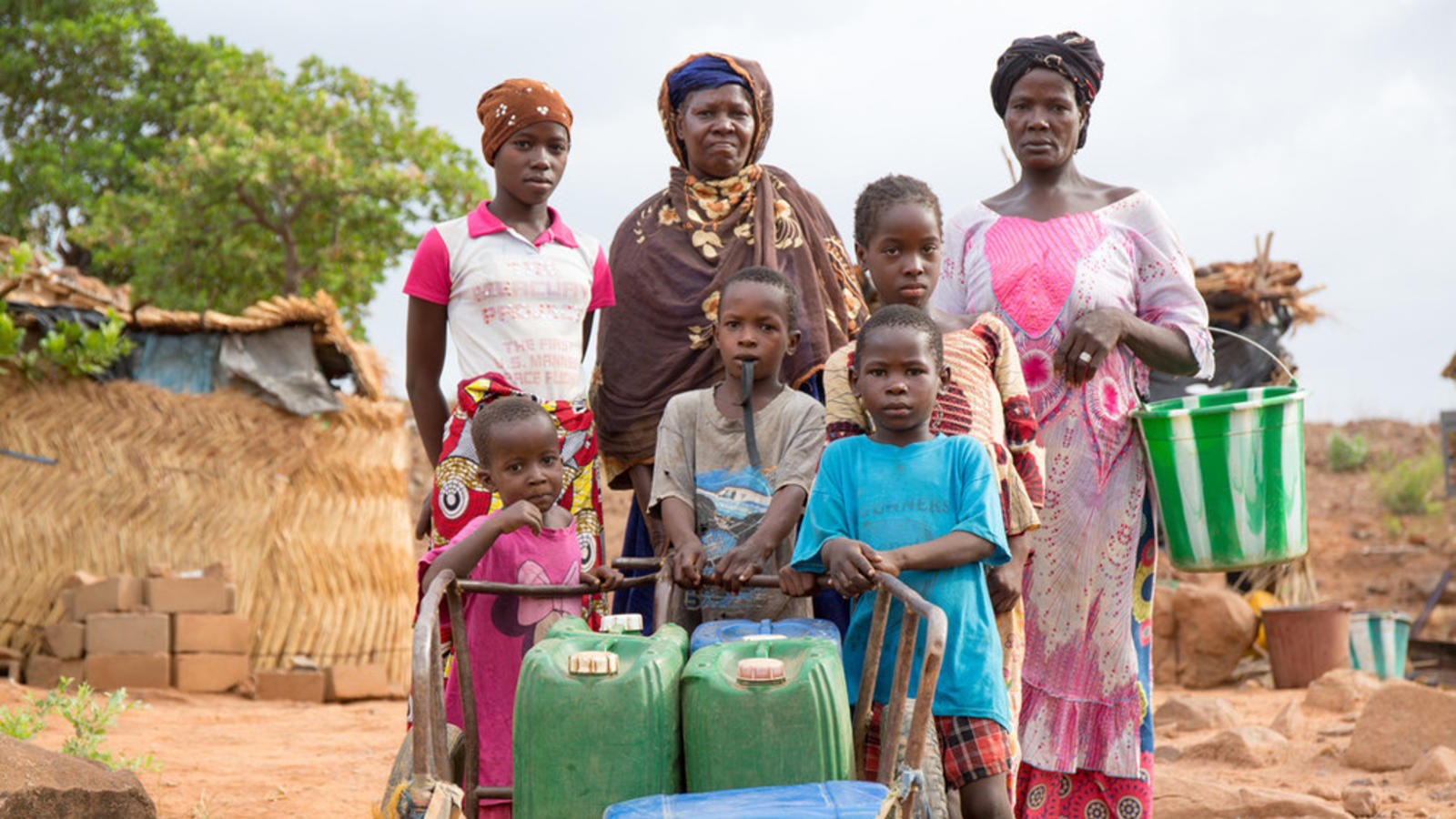 A family in Mali poses with the containers they use to collect water.