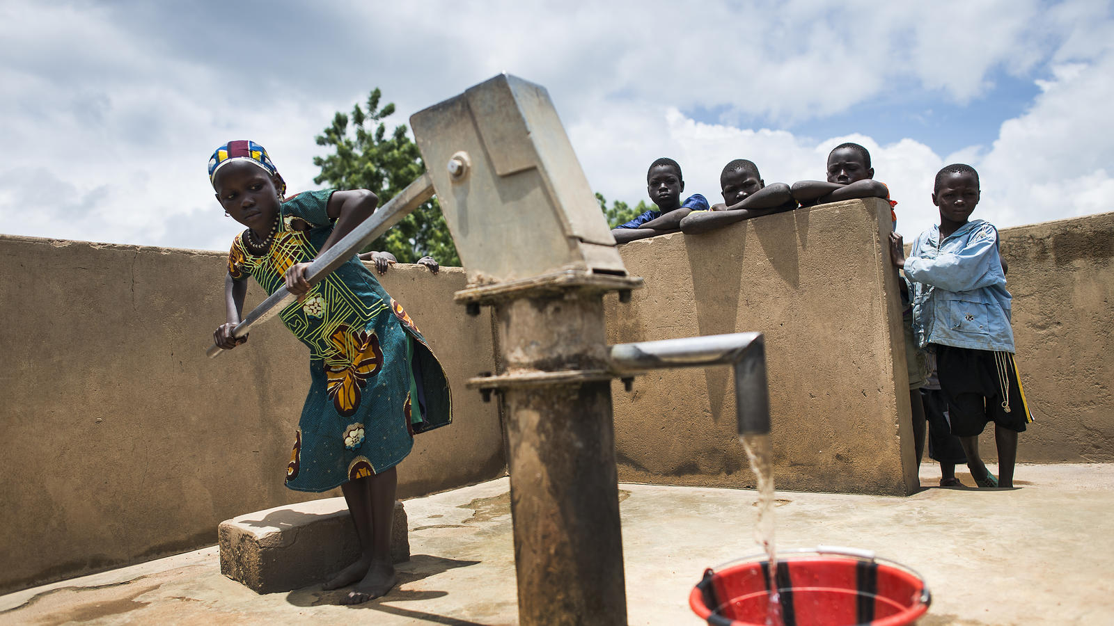 A woman collects water from a pump near her village in Mali.