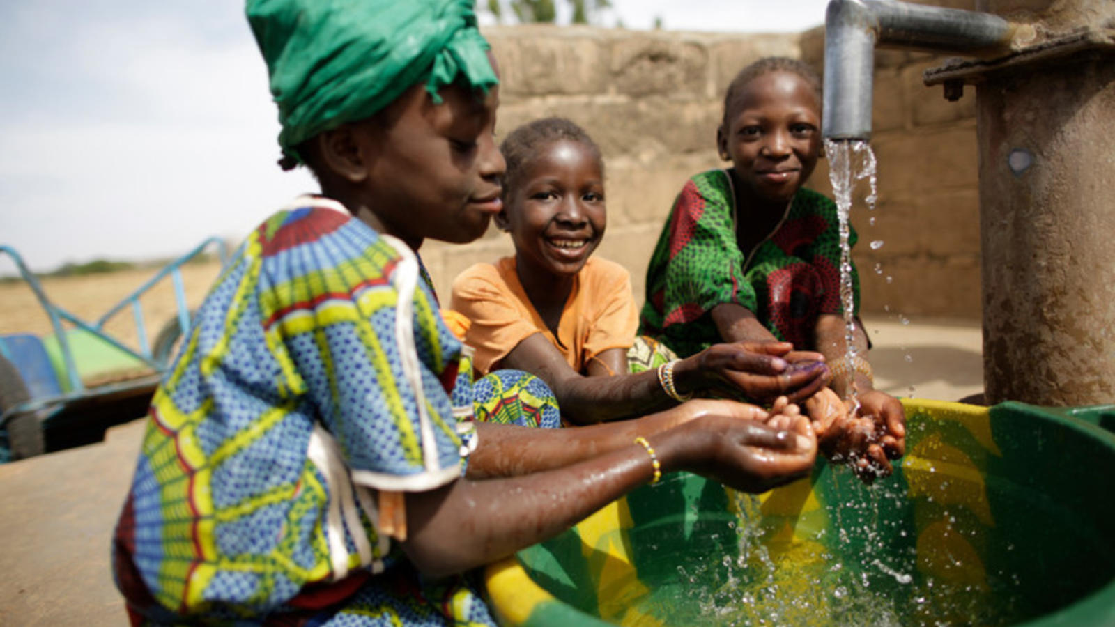 Children enjoying clean water in their village in Mali by splashing around in it.