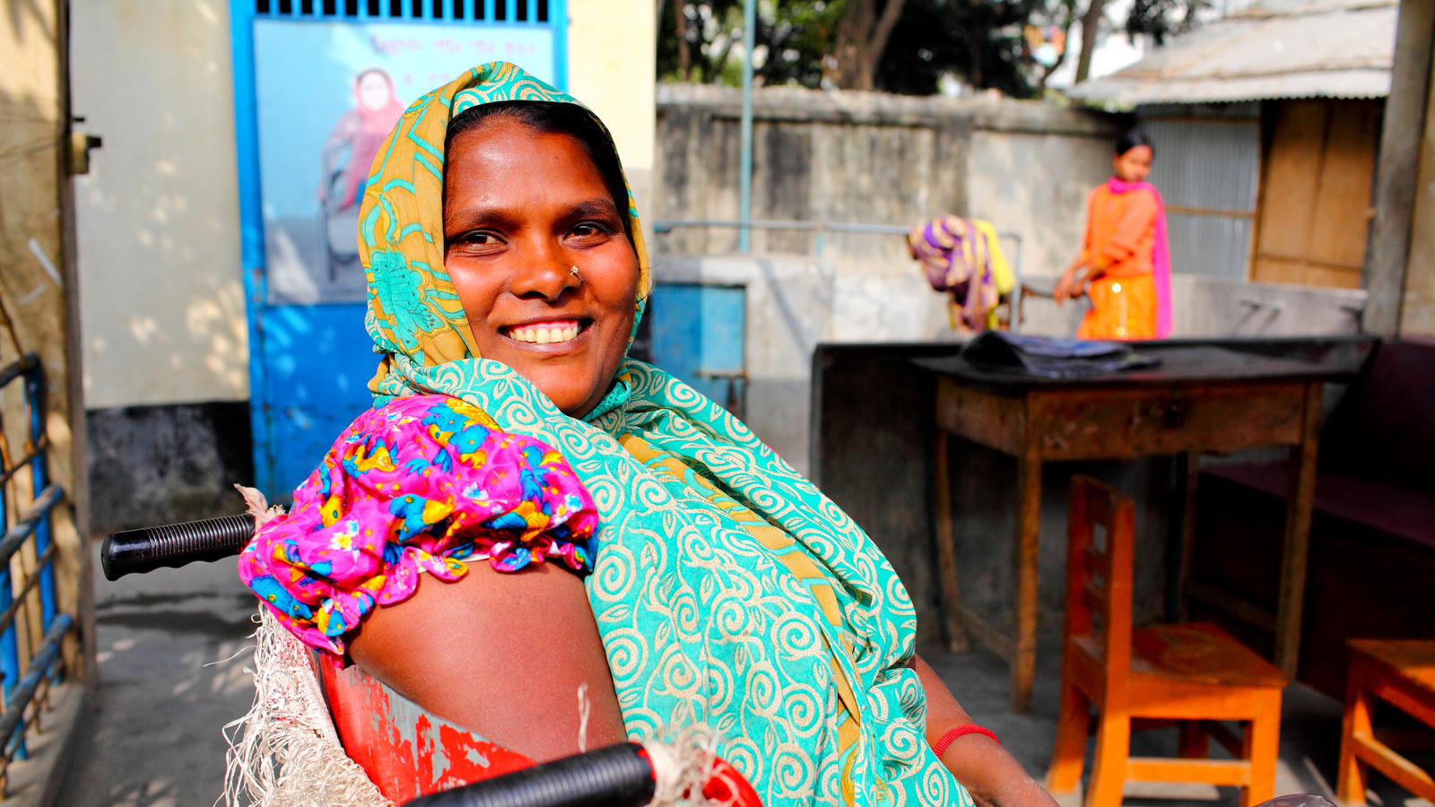 Poppy, a wheelchair user, outside the new disabled latrine block, Bangladesh