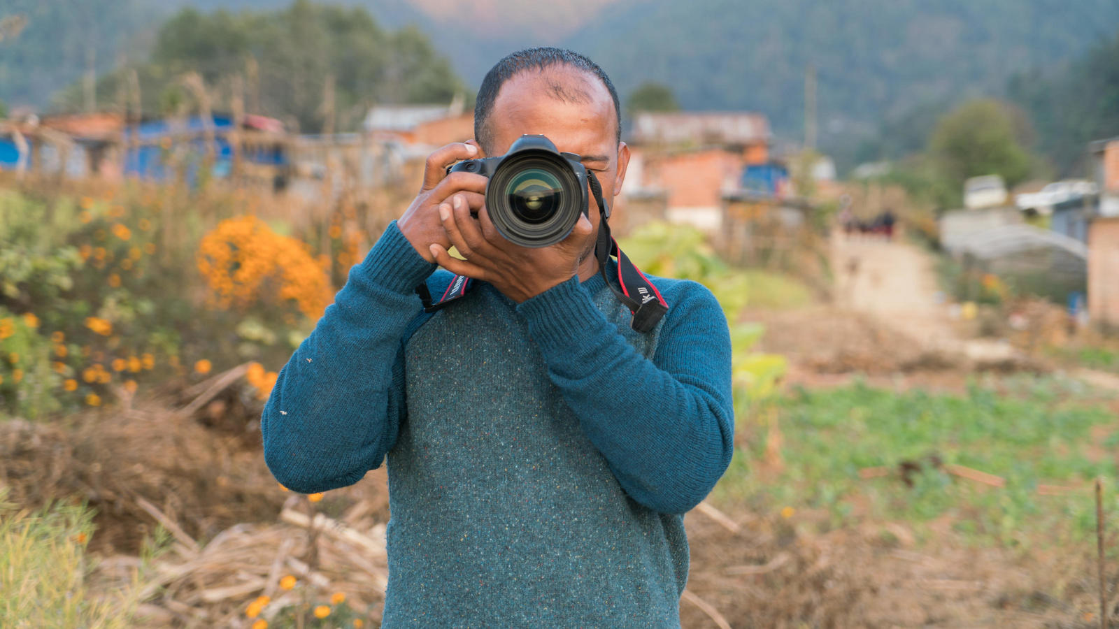 Mani Karmacharya with his camera in the field in Lele, Nepal