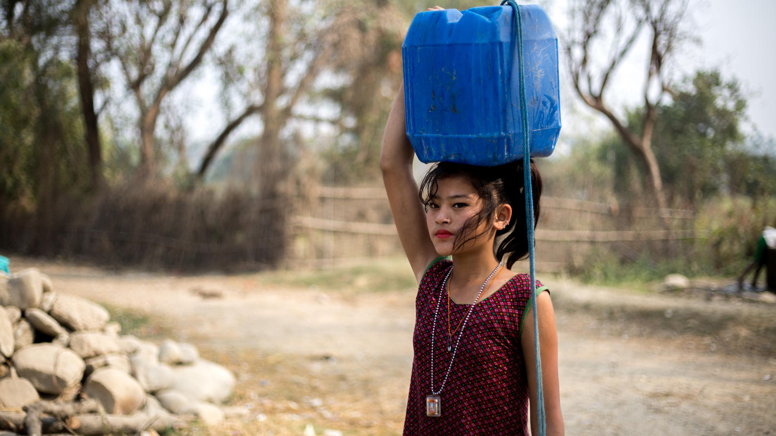 Samjhana carries home a jerry can in Nepal.