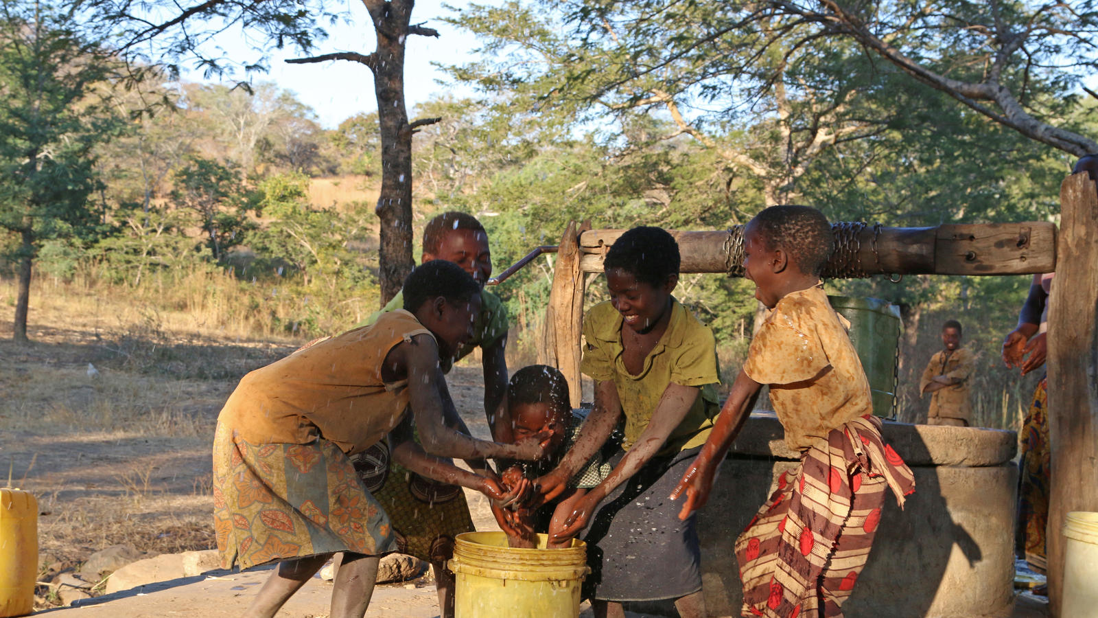 Children enjoying the water from a well at Cheelo Village.