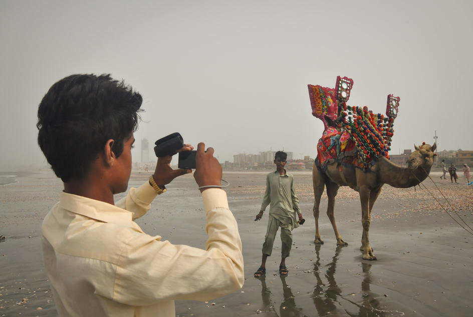 A student has his picture taken with a camel. Thatta, Sindh Province, Pakistan. June 2016.