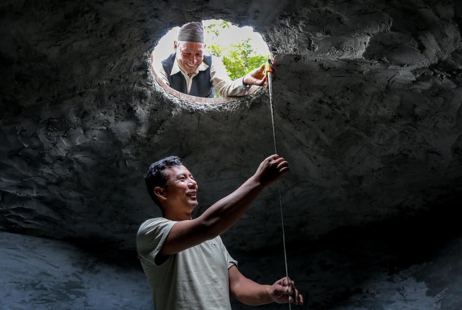 Social Technician, Rajendra Gautam, 33, (down) and Krishna Bahadur Sunuwar, 58, (top) inspecting the technical details inside the sedimentation tank, Koshidekha, Kavre, Nepal, Mar 2017