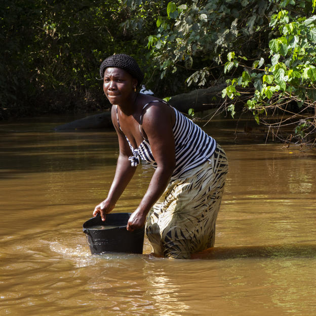 Grace Memsah, 29, collecting water from Nkwaarteng stream, Birim North, Eastern Region, Ghana, November, 2012.