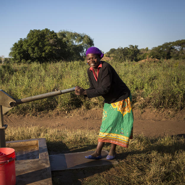 Zione collects clean water at the pump in the village of Chandaka, Malawi