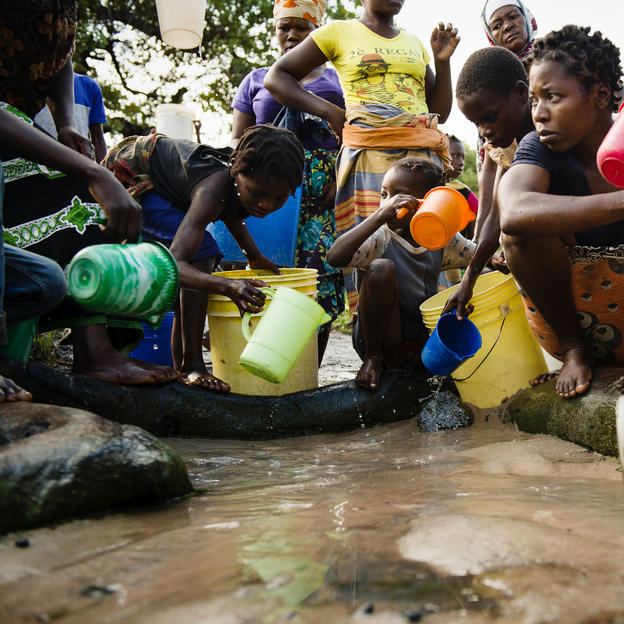 Women and children collect water from an unprotected water source at Nacoto Village, Mossuril District, Nampula Province, Mozambique.