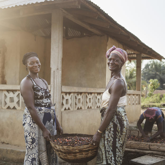 Haja Bobor, 31, left, and her aunt Mamie Ansumana, carrying palm kernels to be dried, in the village of Tombohuaun. Haja has lost three children in the last three years from dirty water. Mamie has looked after her and helped with her grief. Kailahun District, Sierra Leone, May 2017.