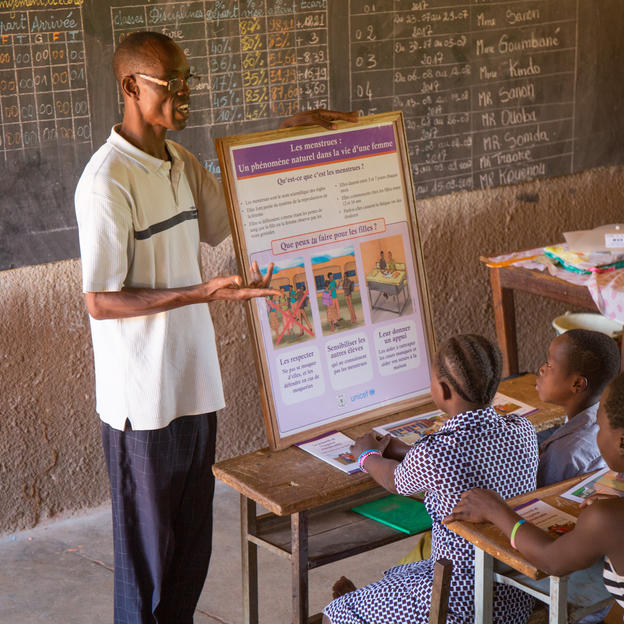 Abel Kouenou, Headteacher, facilitating a menstrual hygiene awareness session in a classroom with pupils, at Peni Primary School, Commune of Peni, Region of Hauts-Bassins, Burkina Faso, July 2018