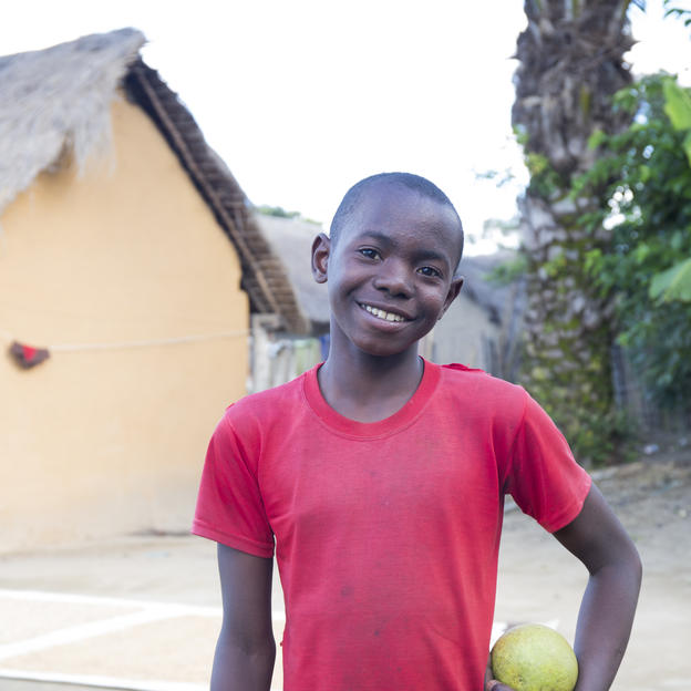 """When we don't have a soccer ball we use a big grapefruit. When I grow up I want to become a driver or a football player."" Stefano, 14, posing with a grapefruit in Mahavoky village, Belavabary commune, Moramanga district, Alaotra Mangoro region, Madagascar. May 2017."