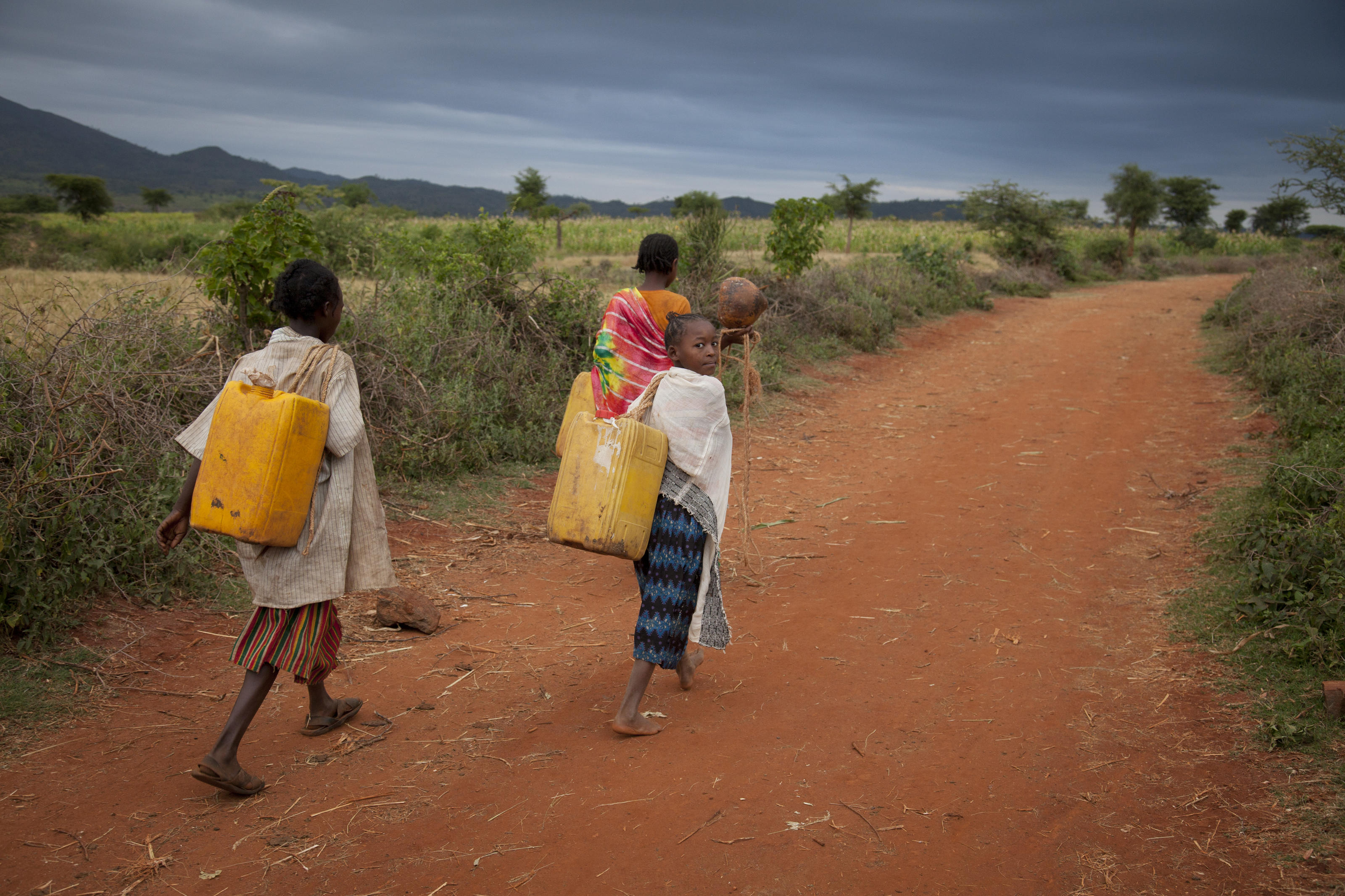 Kawesa Kalabo, around 13, (red skirt, green top, yellow/brown shawl), Meshewat (orange top, noen shawl), Meselech Basaye (red/white top and blue skirt / white shawl on some photos), Ebolaya Kambiro (white shirt/stripy skirt), collecting dirty water in the morning at Orbale river, a good half hours walk away, Lahyte, Konso, Ethiopia, 2012.