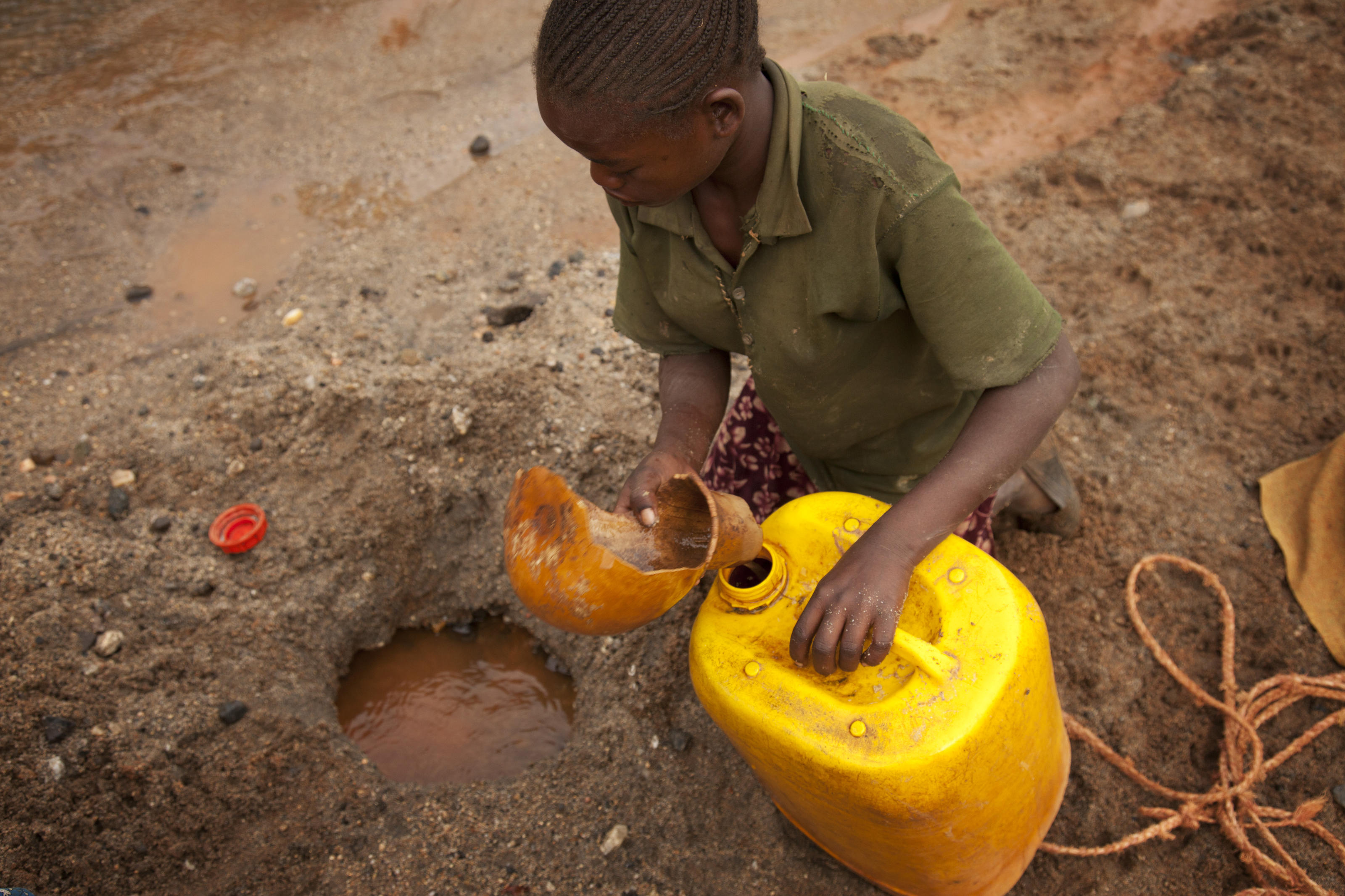 Kawesa Kalabo, around 13, using a calabash to scoop dirty water from the ground, Lahyte, Ethiopia, 2012.