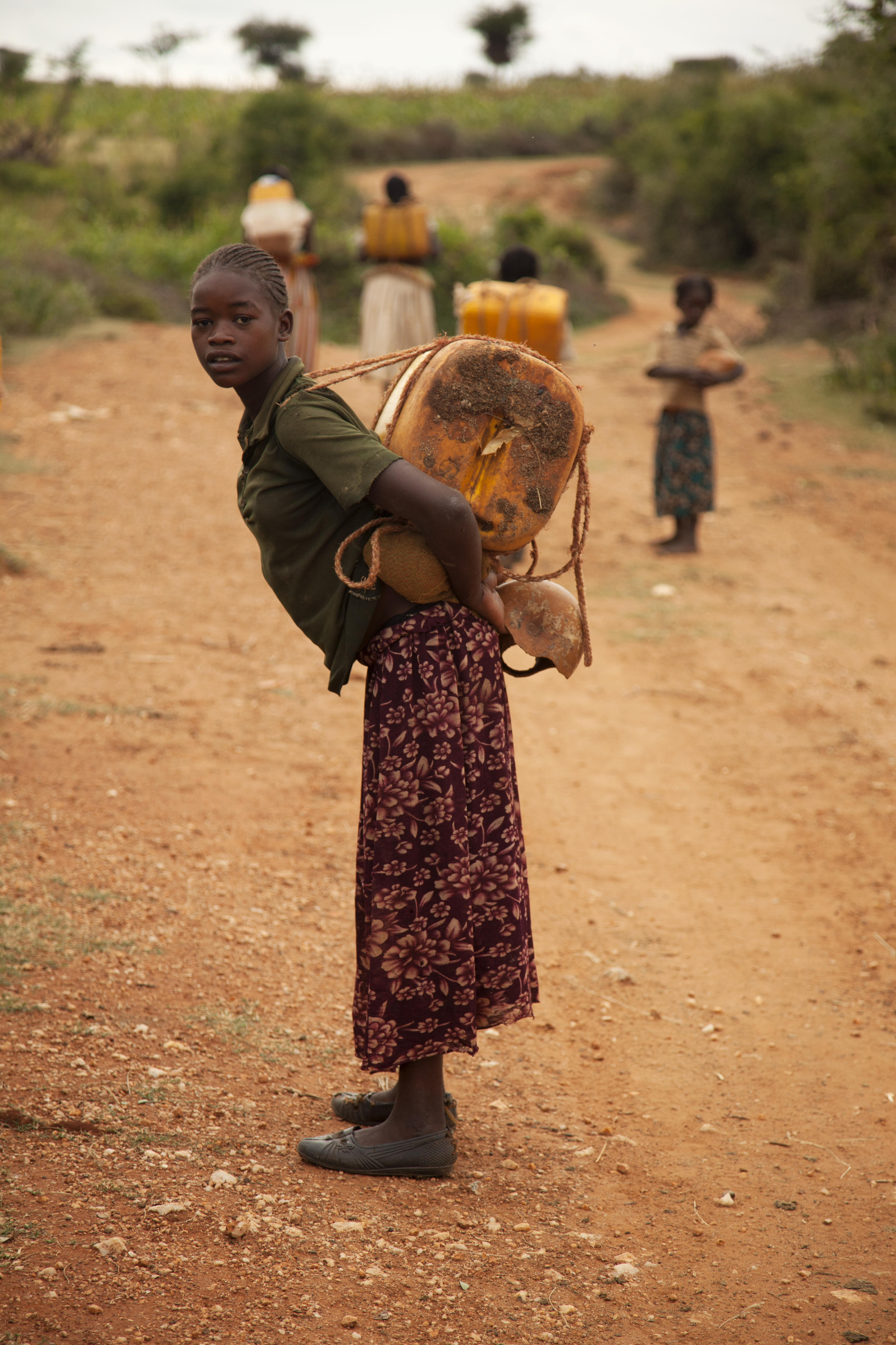 Kawesa Kalabo, around 13, with friends, carrying a jerrycan filled with dirty water back to the village, Lahyte, Ethiopia, 2012.