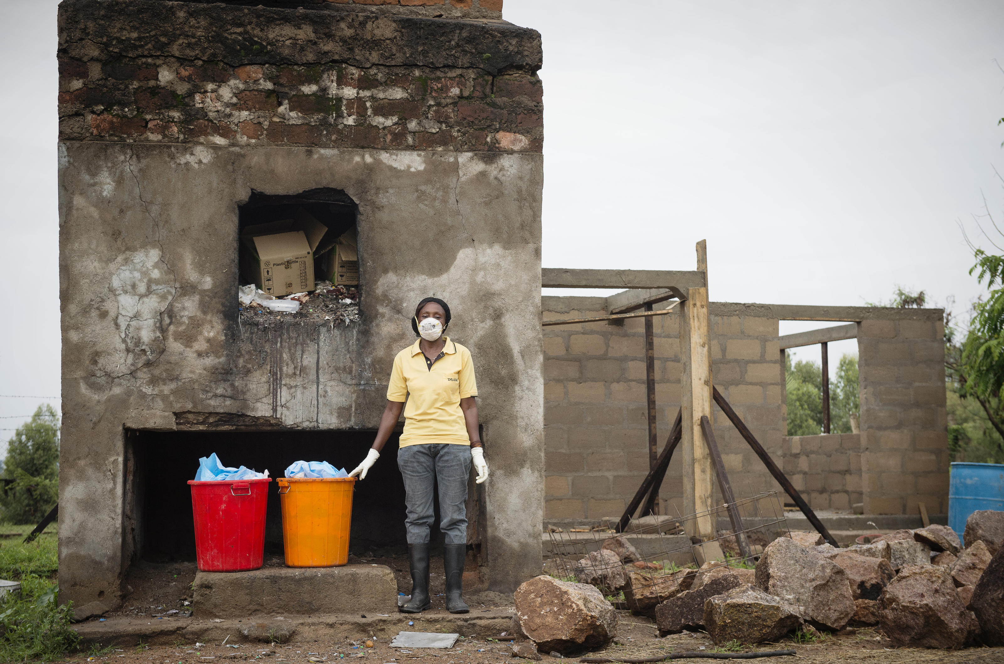 Cleaner Margaret Edson stands in front of the existing incinerator with the new incinerator construction behind, at Kiomboi Hospital, Iramba, Tanzania, December 2015.
