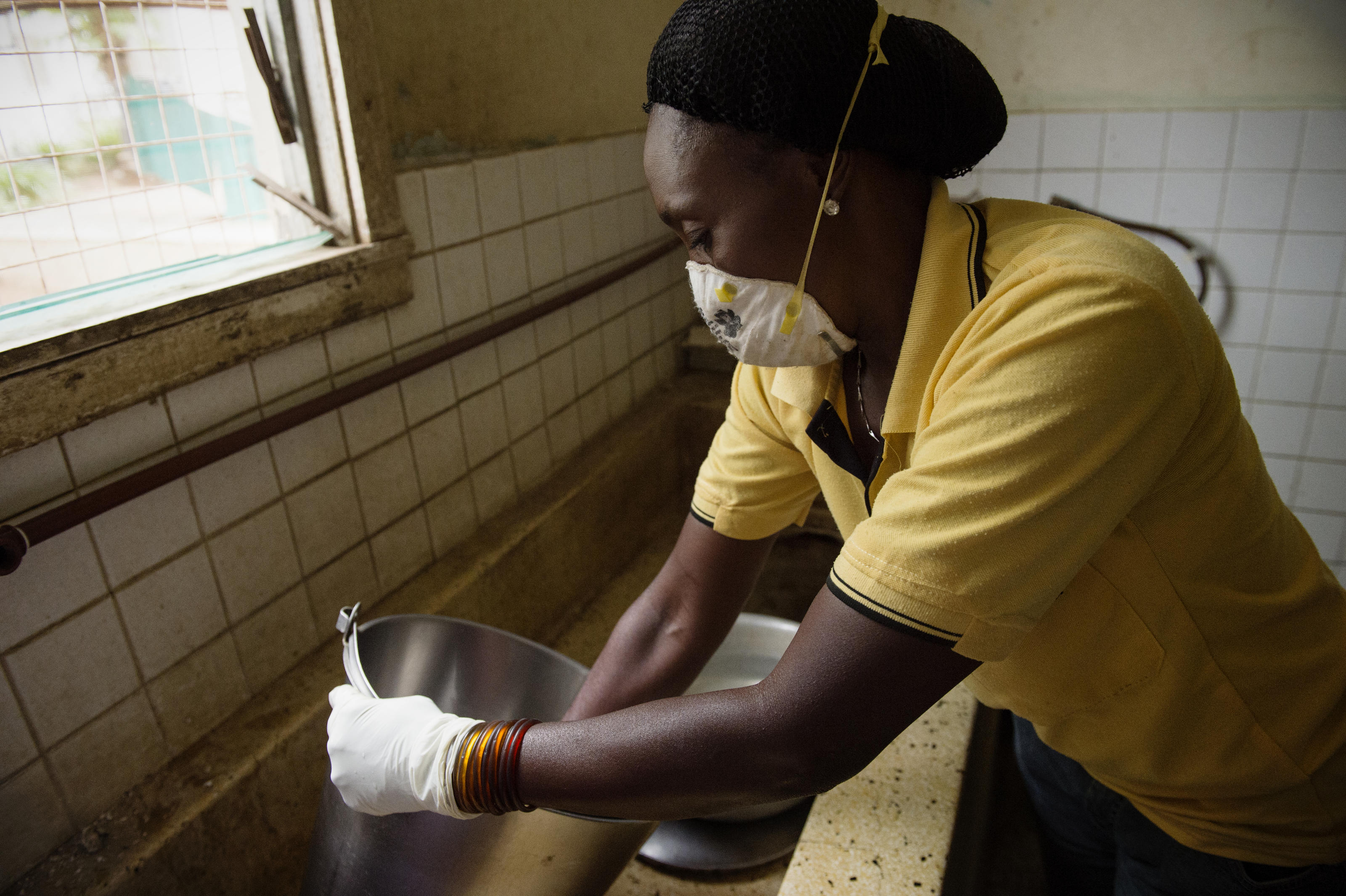 Cleaner Margaret Edson washes buckets in the sluice room at Kiomboi Hospital, Iramba, Tanzania, December 2015.