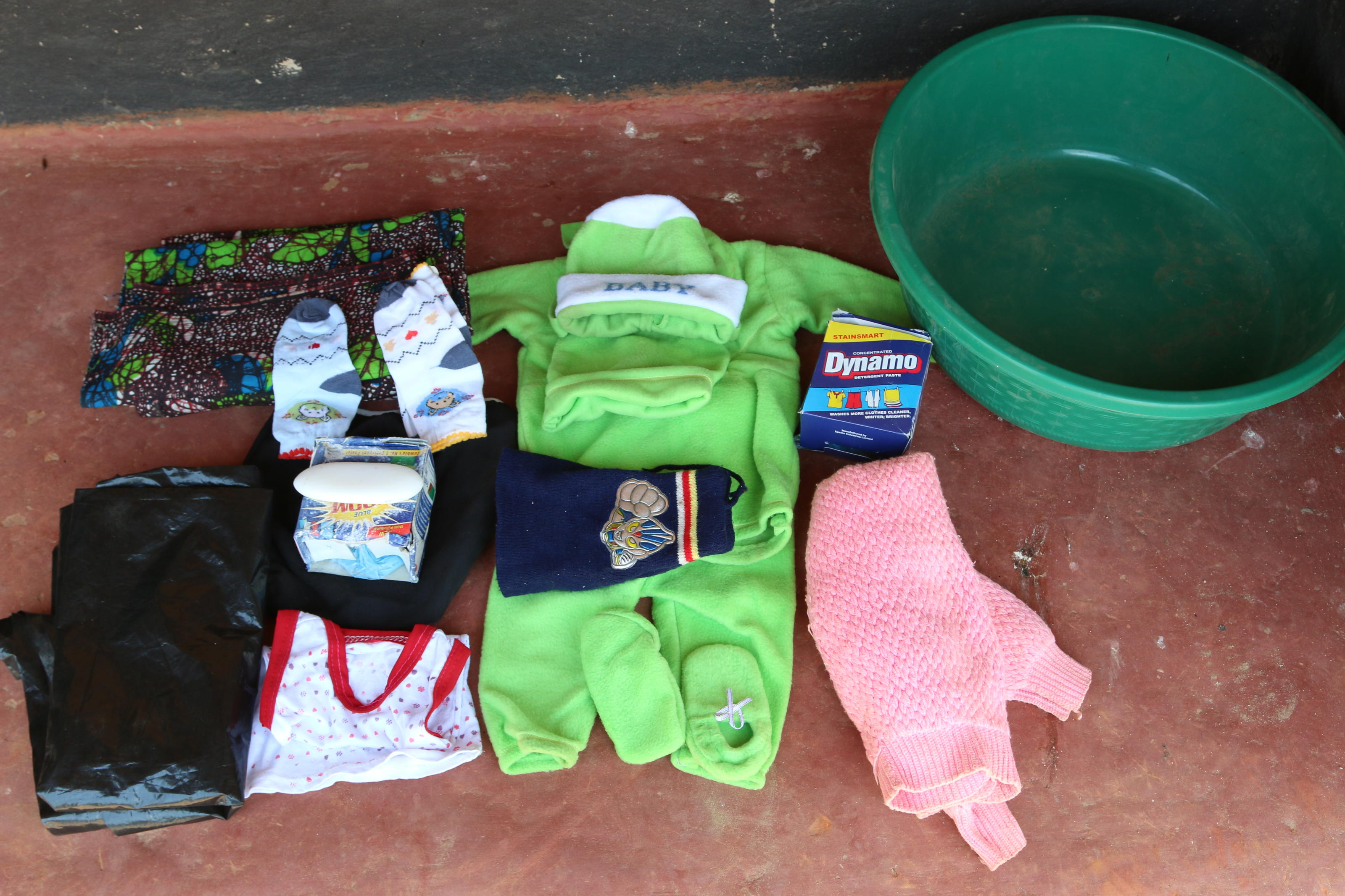 Hazel Shandumba's maternity bag contents: baby blanket, cotton wool, sarong, baby suit, napkins, dish and polythene roll. Hamangaga, Zambia, 2015.
