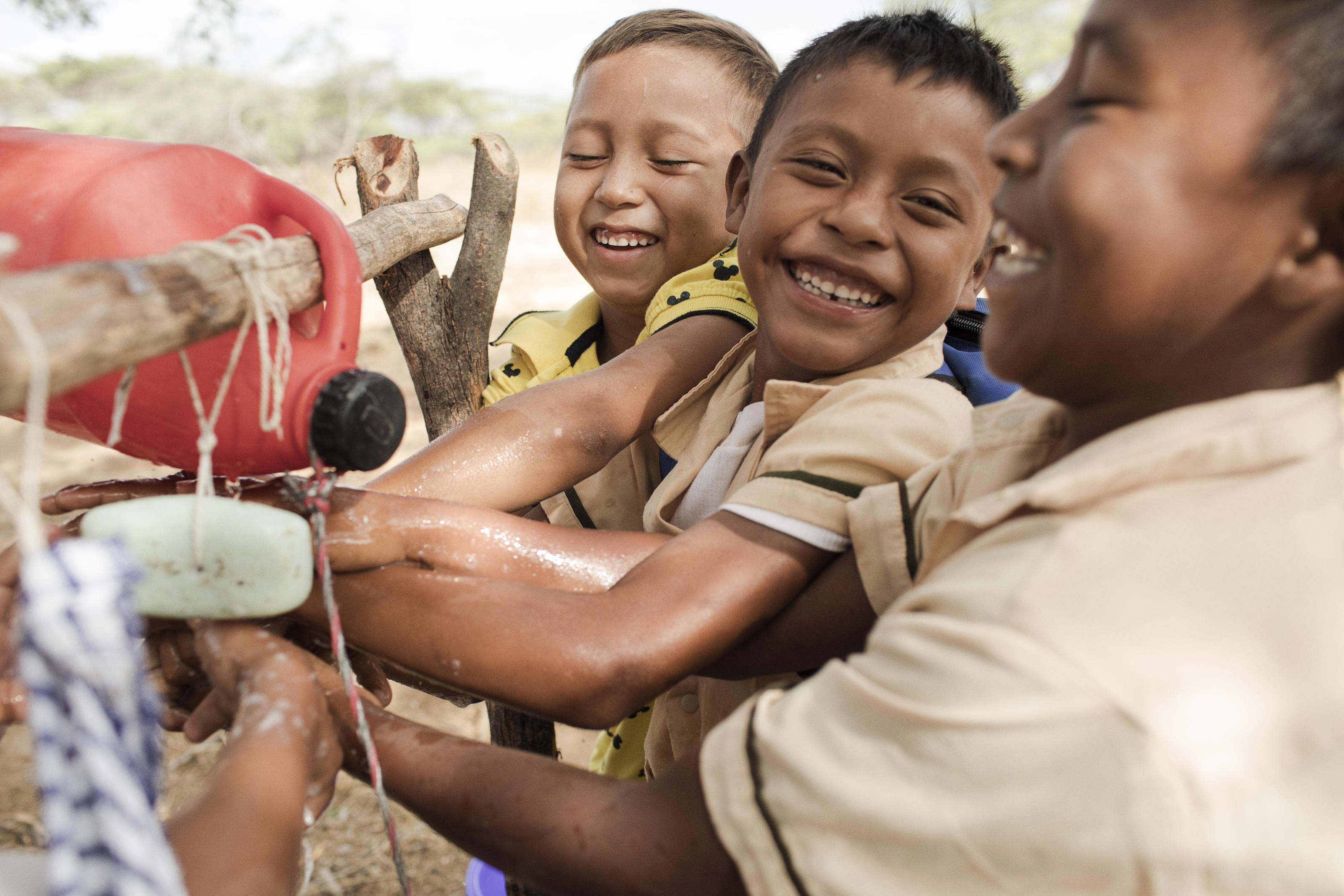 A group of Wayuuma'ana School students wash their hands at a tippy tap in Wayuuma'ana, Maicao, La Guajira, Colombia, March 2017.