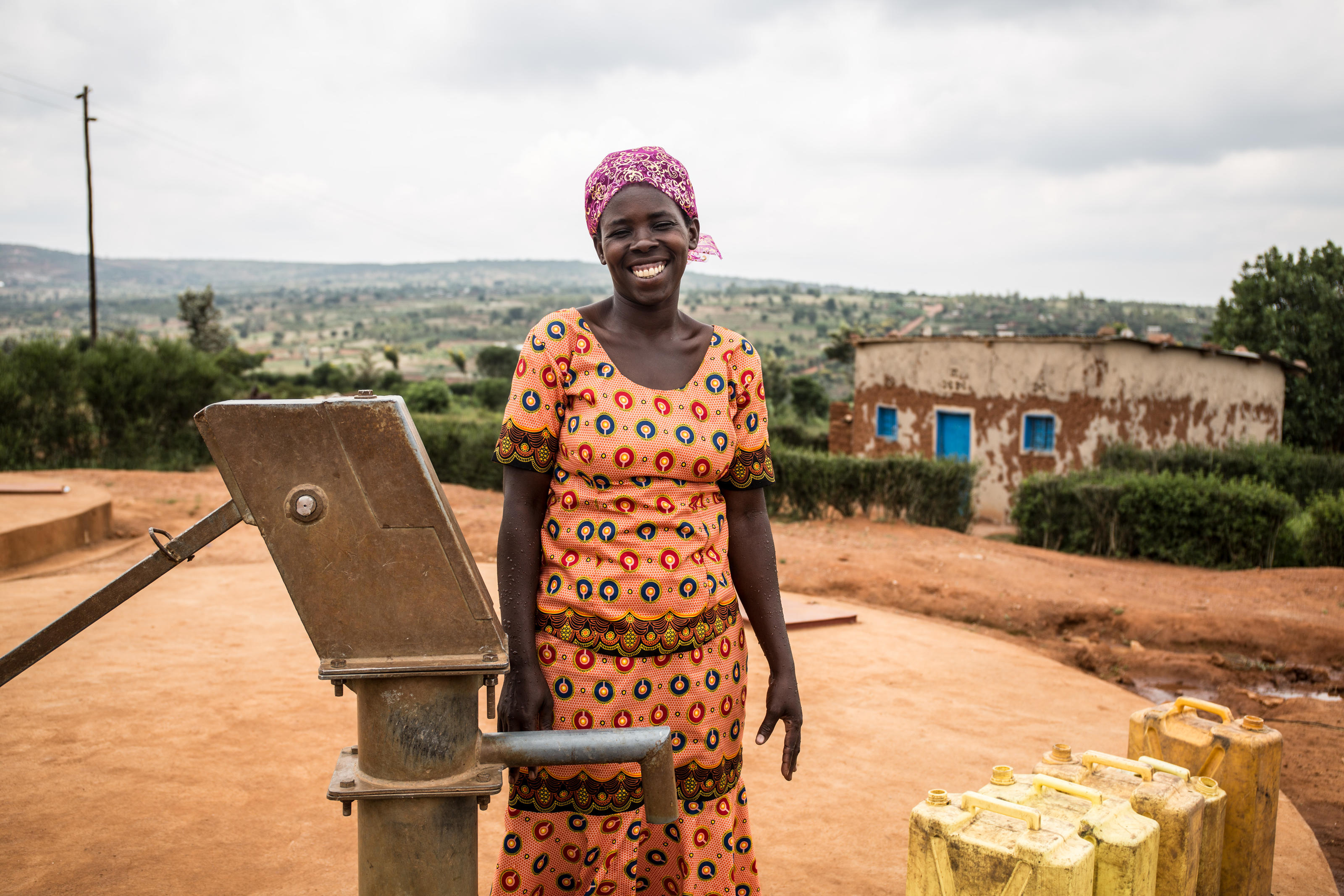 A WaterAid trained pump mechance and local leader, Gaudence Mukahabyarimana, stands next to a handpump in one of the newly built model villages, Nkange, Rwanda, February 2018.
