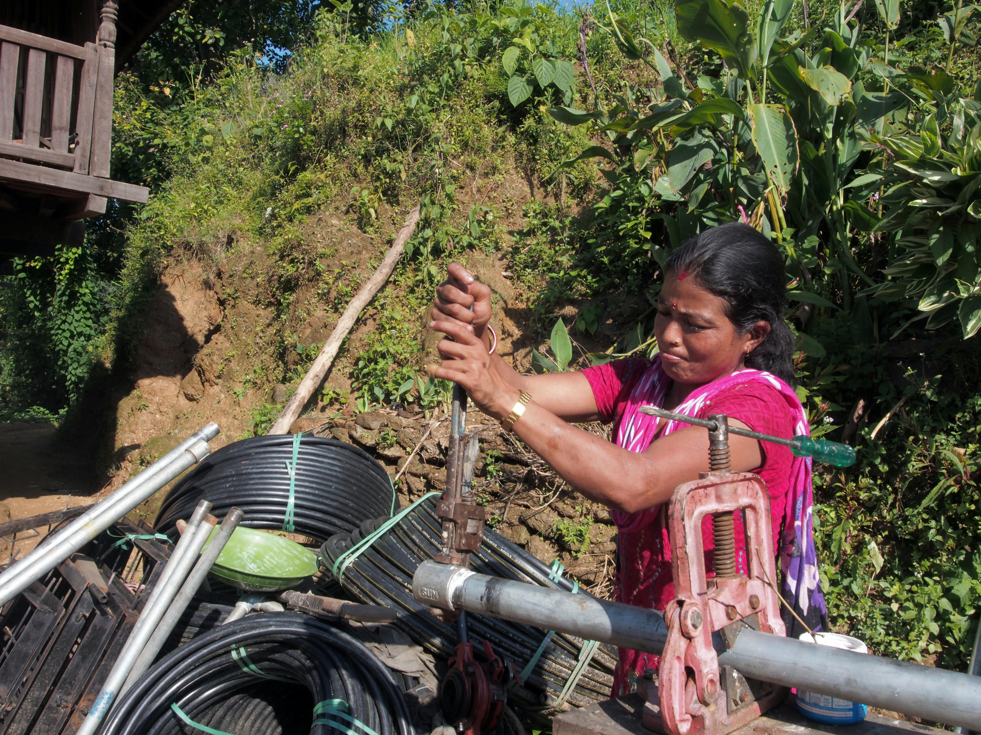 Care taker- Laxmi Bhujel, 29, preparing the pipe fittings. Sajbote Siruwani, Hardeni VDC, Udayapur, Nepal, Sep 2014