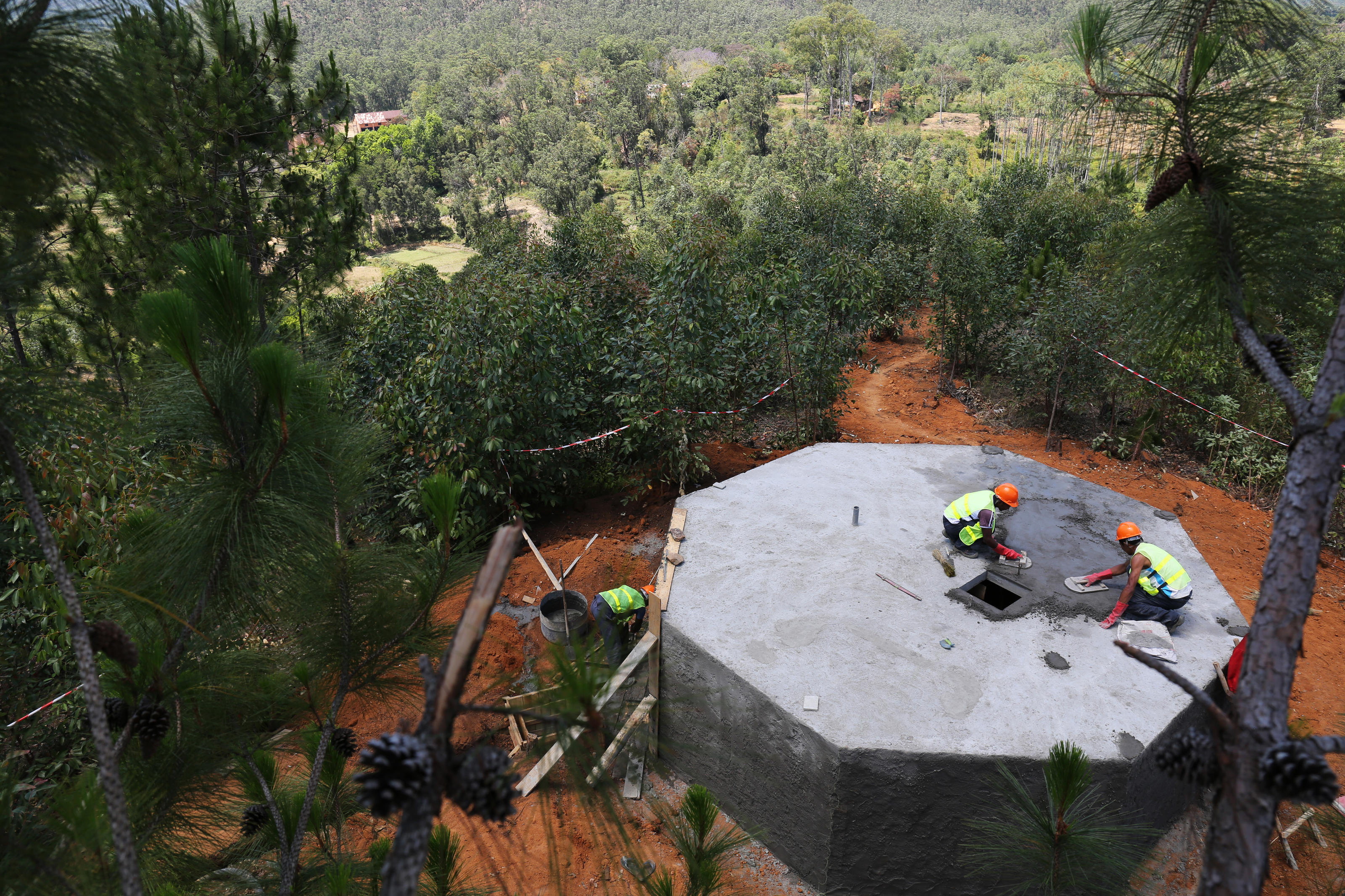 Further up, masons working at the 45 cubic meter water tank in Tsarafangitra Village, Belavabary Commune, Moramanga District, Alaotra Mangoro Region, Madagascar. October 2017.