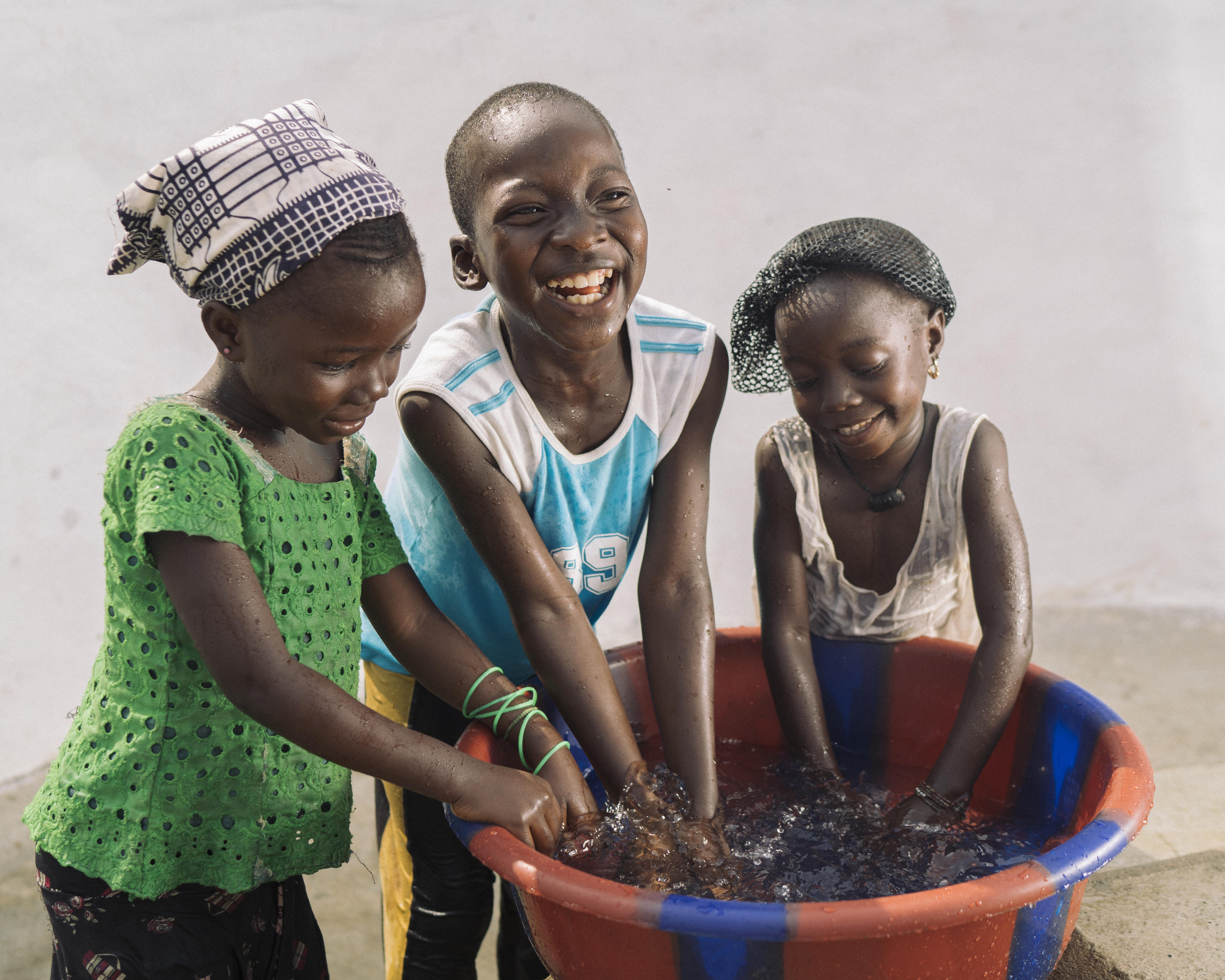 Kokoyeh, 8, Nancy, 6, and Lucy, 5, play with the clean water as their way of celebrating the new water pump, in Tombohuaun, Kailahun District, Sierra Leone, January 2018.
