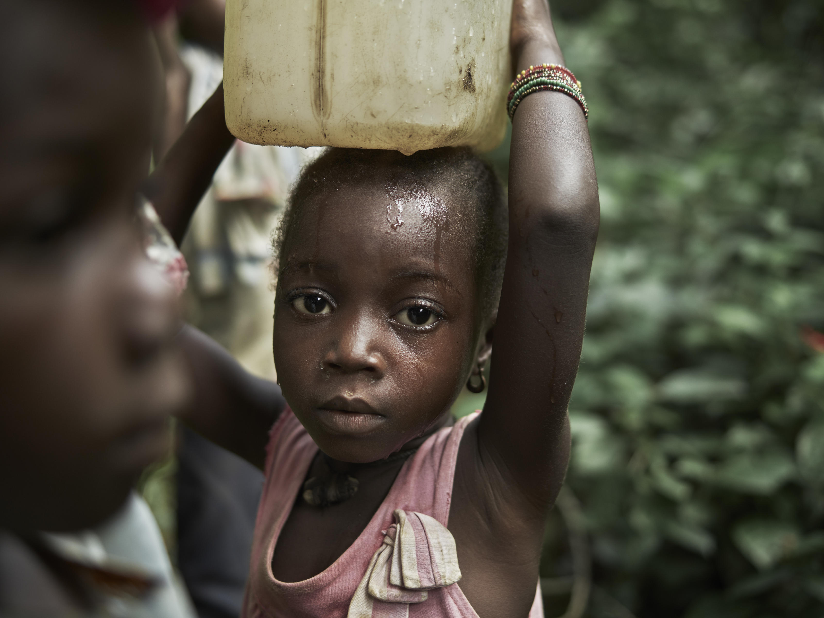 Nancy Smart, 6, carrying a container, called a 'gallon' of dirty water collected from a natural spring - the previous water source for the community of Tombohuaun. The gallon is put on her head by her mother Fatu, whom she goes with to collect water,  ...