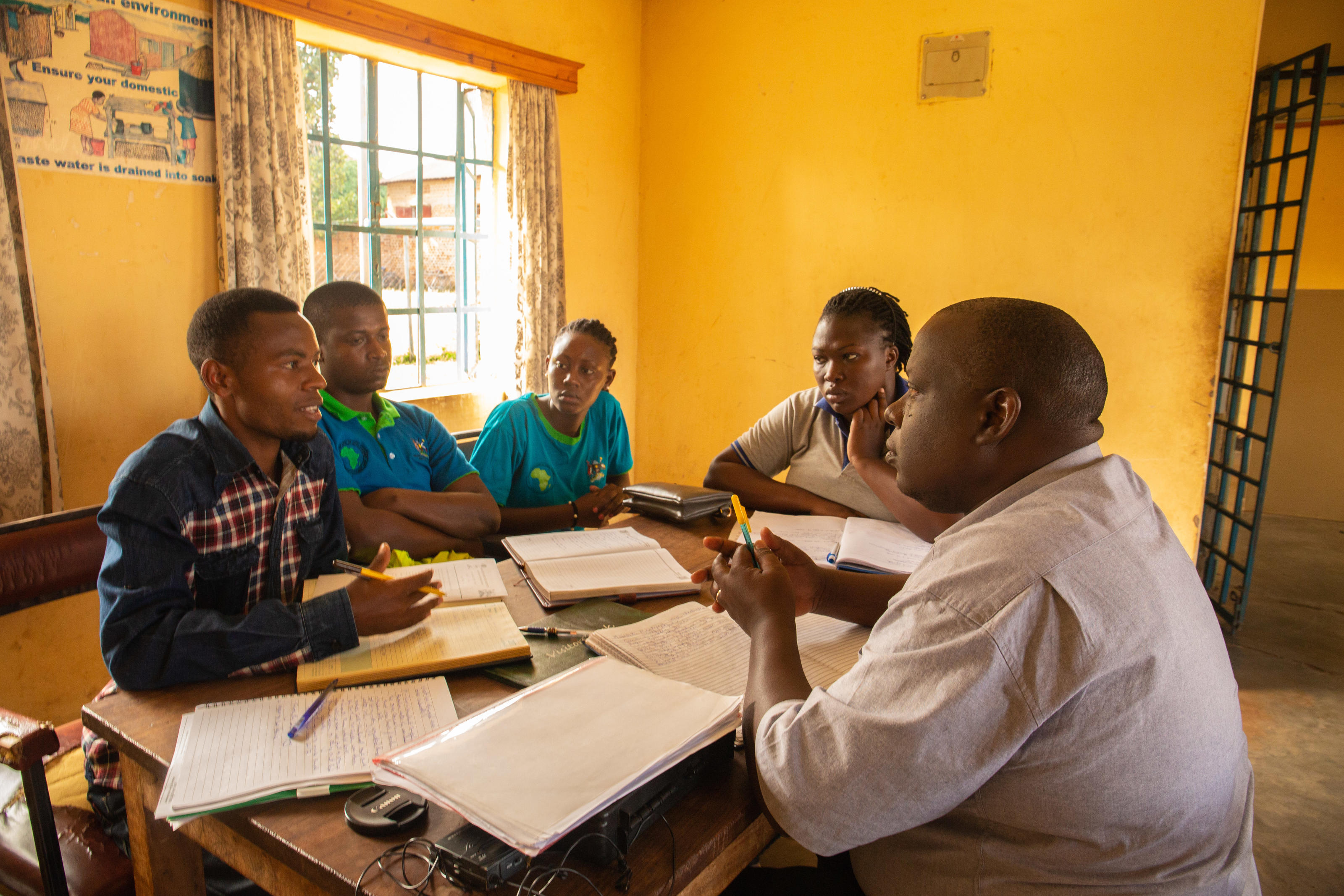 Right: Nkundizana Julius, 25, Team Leader, Busolwe Piped Water Supply System, meeting with Eastern Umbrella for Water and Sanitation and WaterAid staff , Busolwe Town Council, Butaleja District, Uganda, November 2018.