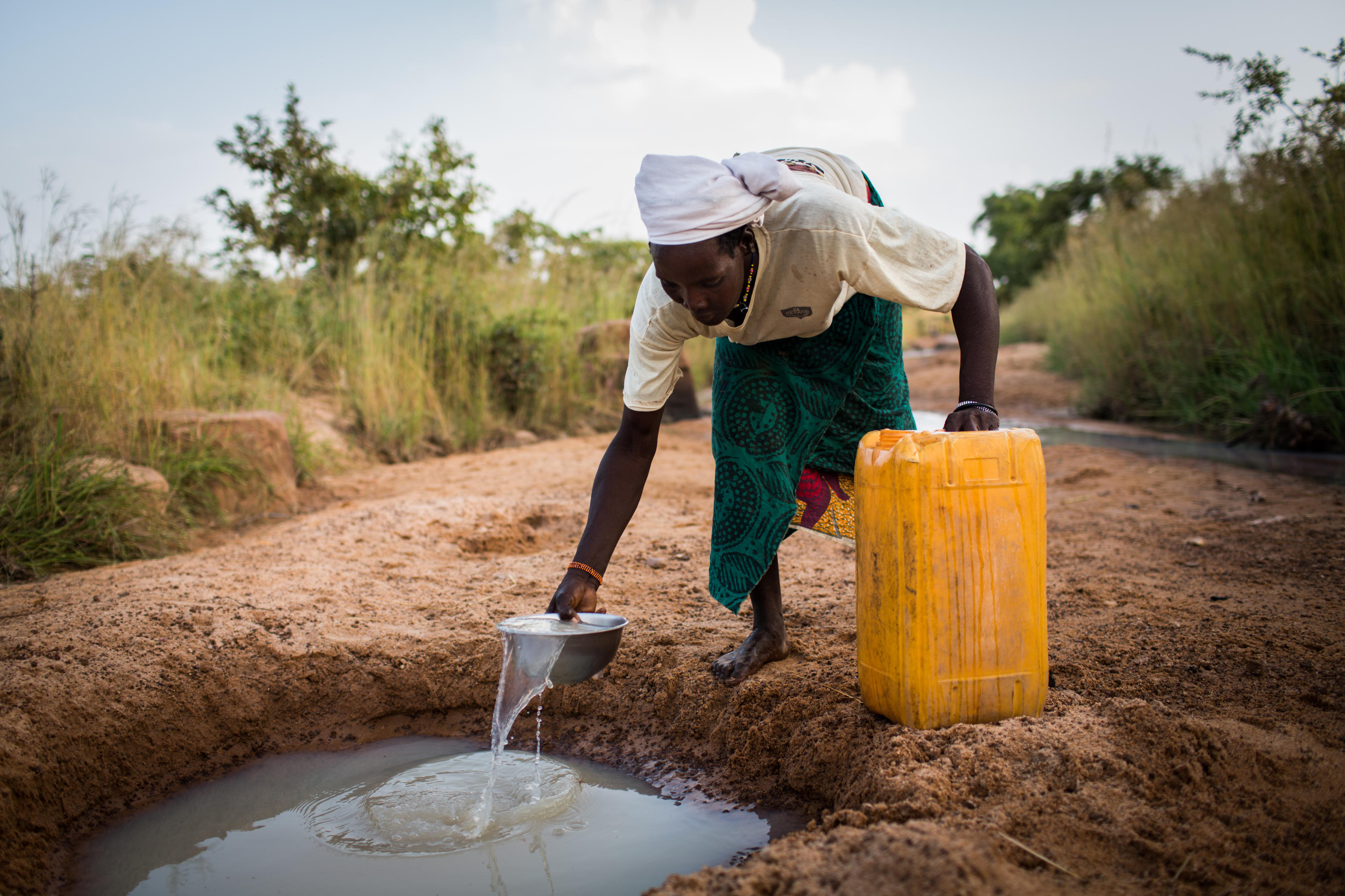 Sawadogo Lamoussa, 42, collects dirty water from a partially dried riverbed in Imbina, Burkina Faso, October 2014.