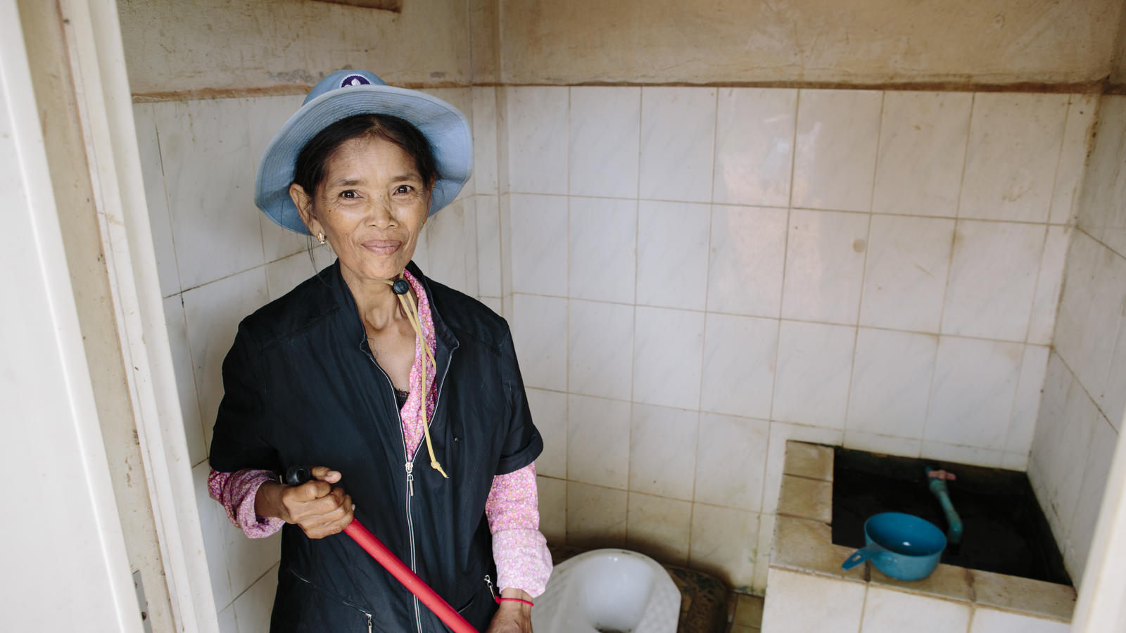 Cleaner Met Pov, 52, works on the patient toilets at Thmor Kol Referral Hospital, Battambang, Cambodia.
