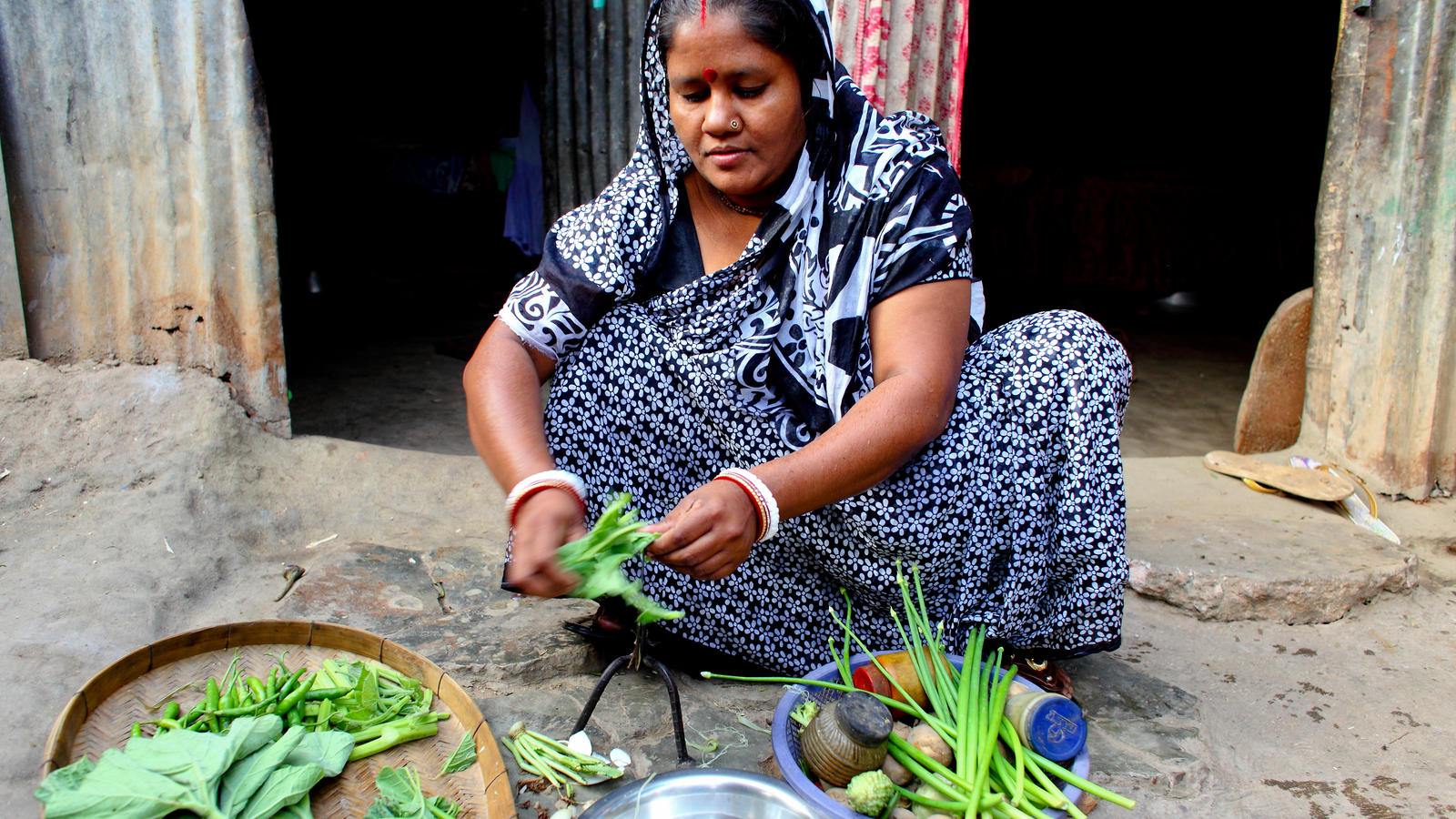 Bashona Sharkar, 40, Secretary of the Community Based Organisation, preparing food with clean water from the new water point in Kalshi Takar Baa slum, Dhaka, Bangladesh, 2011.