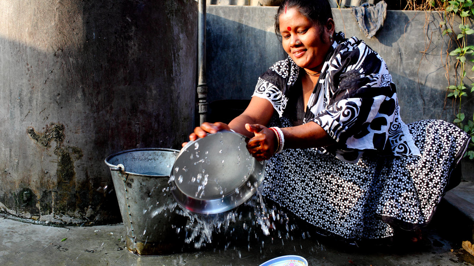 Bashona Sharkar, 40, Secretary of the Community Based Organisation, washing her dishes in clean water from the new water point in Kalshi Takar Baa slum, Dhaka, Bangladesh, 2011.
