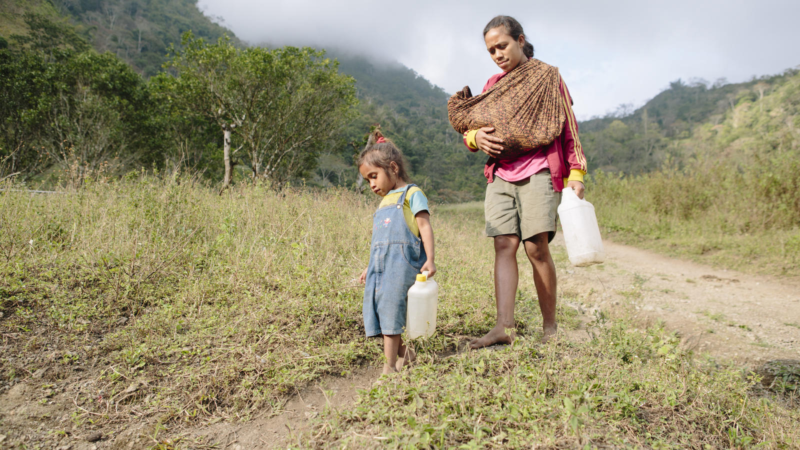 Filomena and her daughter Fidelia on their way to collect water from an unsafe stream in Timor-Leste.