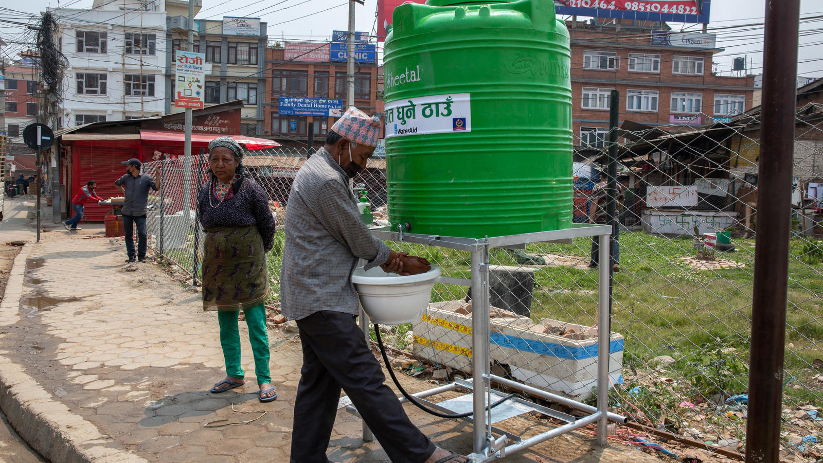 A local resident washing his hands using the contactless handwashing station at Lagankhel bus station, Lalitpur, Nepal, April 2020.