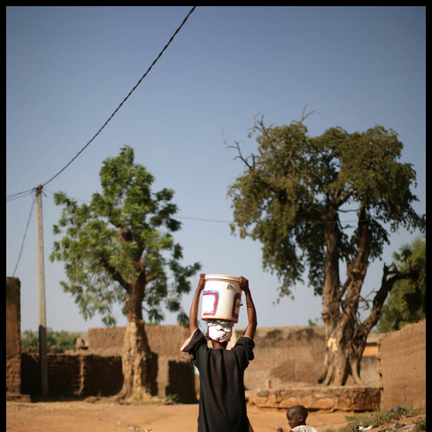 Woman carrying water, with two children, Nafadji, Bamako, Mali