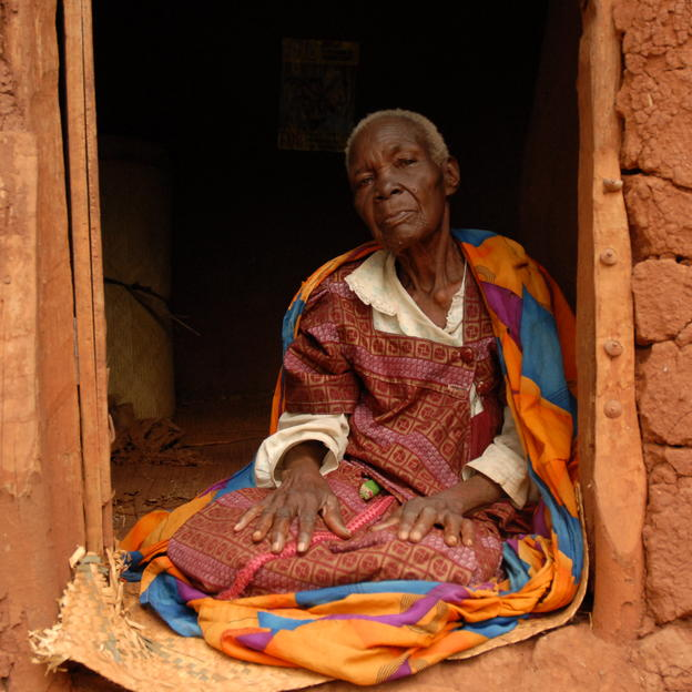 Dolatia Namoudu sitting inside the doorway of her house, Kitayita, Wakiso, Namayumba, Uganda