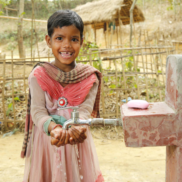 A girl washes her hands and face with soap and water at a water tap, installed with the support of HSBC and WaterAid, at Gulni Tea Estate in Sylhet District, Bangladesh. February, 2017.