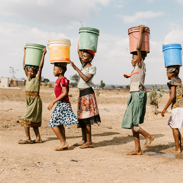 Girls carry water away from a privately owned shallow well on the edge of Nyarugusu. This is the closest water source to Nyarugusu Dispensary, a 15-min drive away; the well runs low in the dry season and is subject to contamination in the rainy season. Nyarugusu, Geita District, Tanzania.