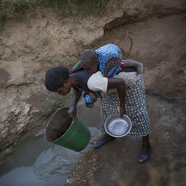 Esnart Phiri, 21, with her son Jafali Lloyd, 1 year 2 months, on her back, collects dirty water from an unprotected spring in the village of Vimphere, Kasungu District, Malawi, June 2016.