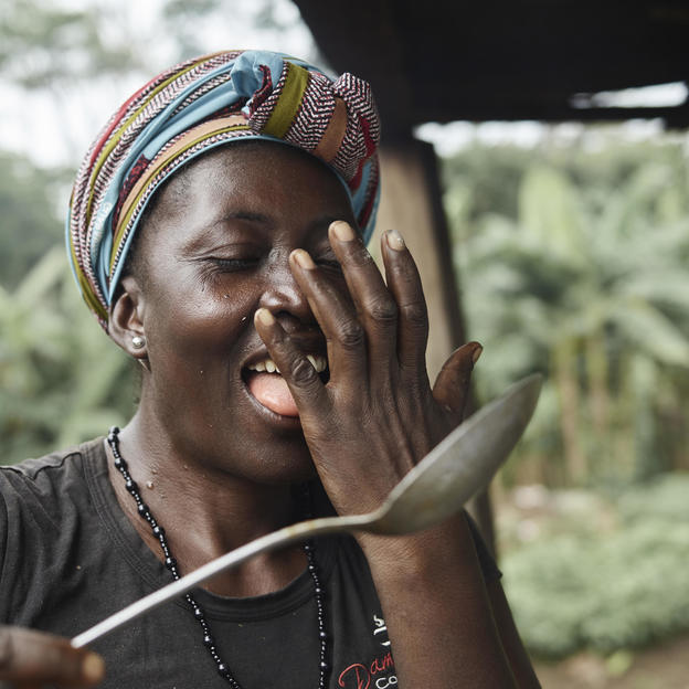 Matu, 40, tastes a stew she has made on the side of their hand, which is the traditional way of testing food, in Tombohuaun, Kailahun District, Sierra Leone, May 2017.
