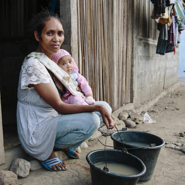 Eliza Fatima Ornai, 30, and her 5 month old daughter Nelsia Marica Ornai with the dirty water she collects from a stream, Tatekar, Manufahi District, Timor-Leste, 2015