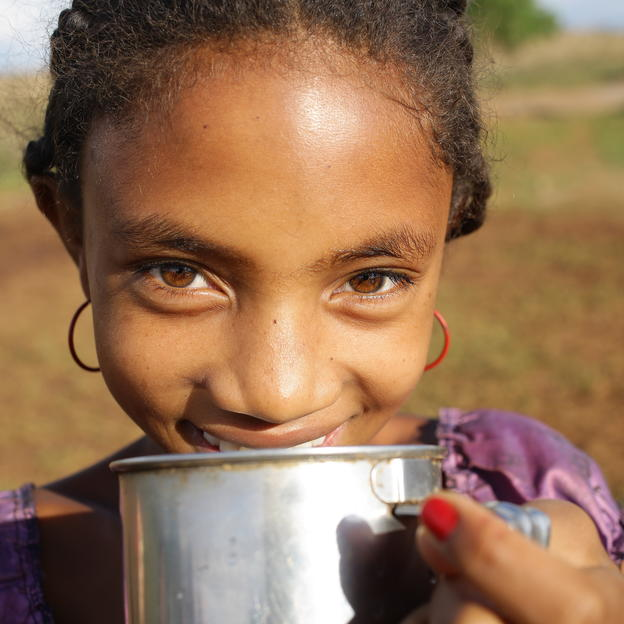 """Having enough water in our village makes us cleaner and less tired."" Aurelia, 12 years old, drinking clean water at their temporary water point in Manakambahiny village. Bevato commune, Tsiroanomandidy district, Bongolava region, Madagascar. December 2016."