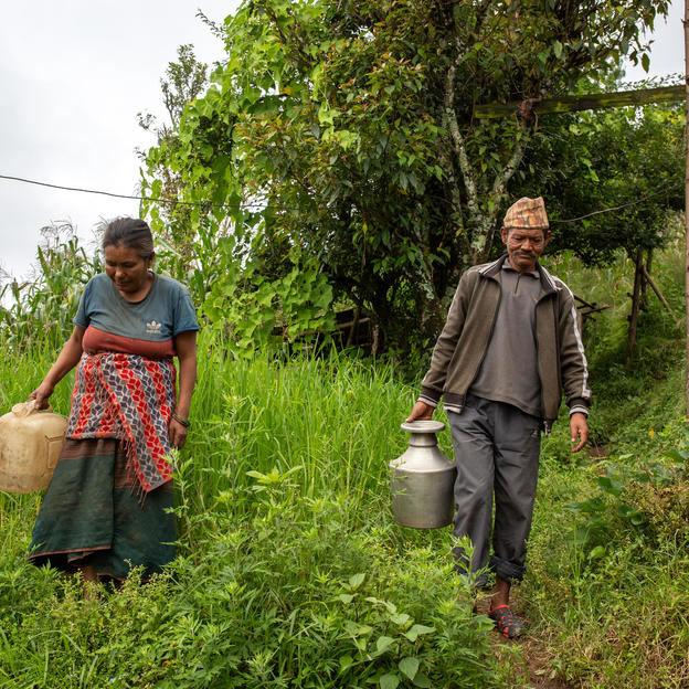 Dhol Kumari Shrestha, 52, with her husband Chakra Bahadur Shrestha, 65 (Right), heading towards the water source to fetch water. Bimjet, Sayapati, Shailung Rural Municipality-4, Dolakha, Nepal, September 2018.