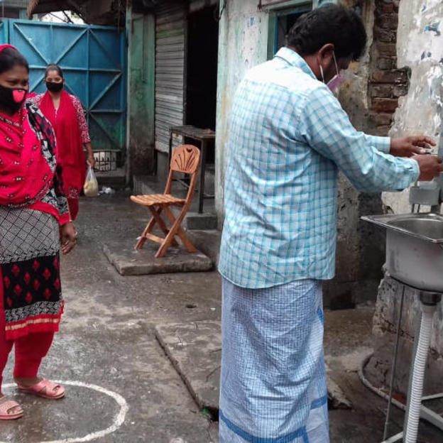 Handwashing at the contactless portable device at the community entry point. Contactless (with paddle) handwashing device- a low cost yet highly effective solution for low income communities. Covid-19 response. Bangladesh. April 2020