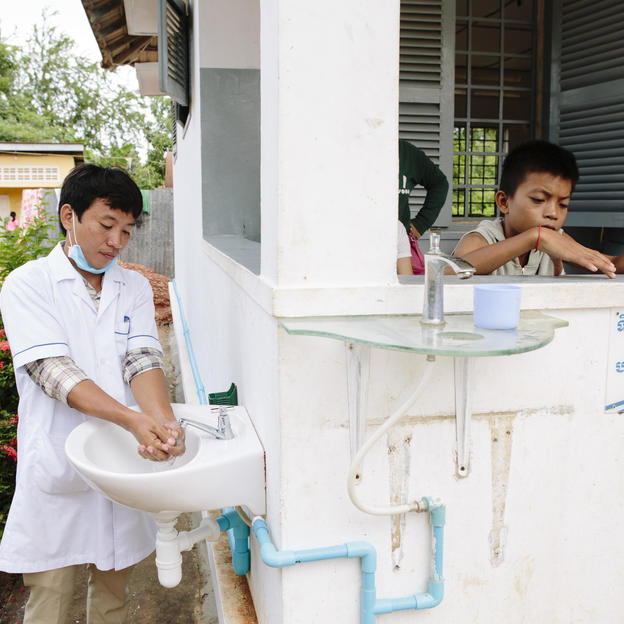Nurse Peu Aranhya, 30, washes his hands in clean water at a sink, Thmor Kol Referral Hospital, Battambang, Cambodia, August 2016.