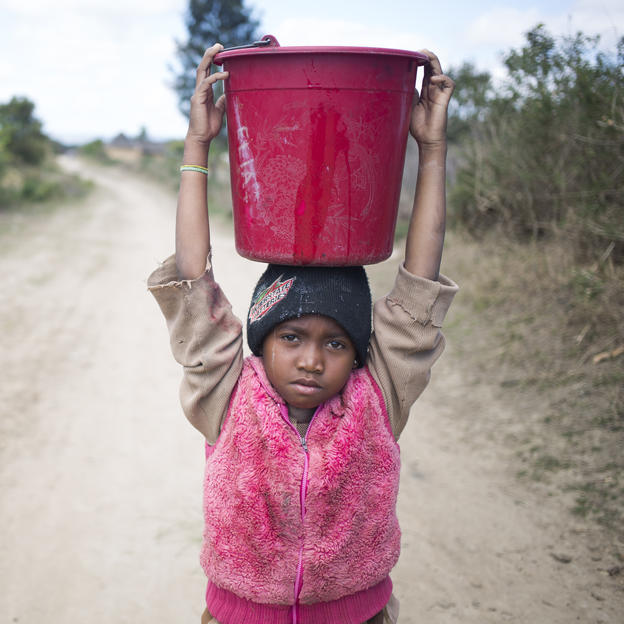 Portrait of Nirinasoa called Neny, eight years old with a bucket full of dirty water on her head _ on her way back home from the dirty water source. Tsarafangitra village, Belavabary commune, Moramanga district, Alaotra Mangoro region, Madagascar. September 2016.;