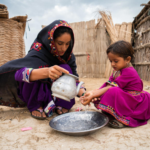 Roshna, 19, helping her child Kainat, 3, to wash her hands in the villlage of Muhammad Urs Sehejo, Chatto Chand Union Council, Thatta District, Sindh Province, Pakistan, September 2018.