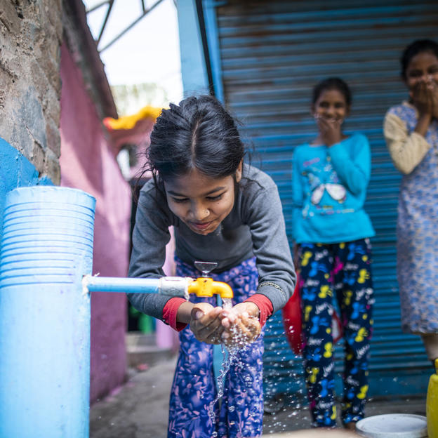 Sneha (10) drinks water from an installed standpost in Raghubir Nagar, New Delhi, India. 12 March 2020