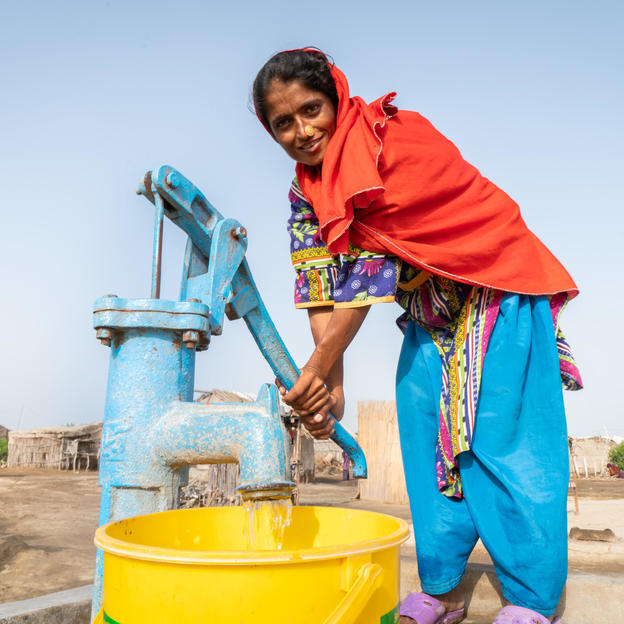 Zainab, 35, fetching water from a WaterAid installed pump in the village of Tamachi Mallah, Union Council Doomani, District Thatta, Province Sindh, Pakistan, May 2018..